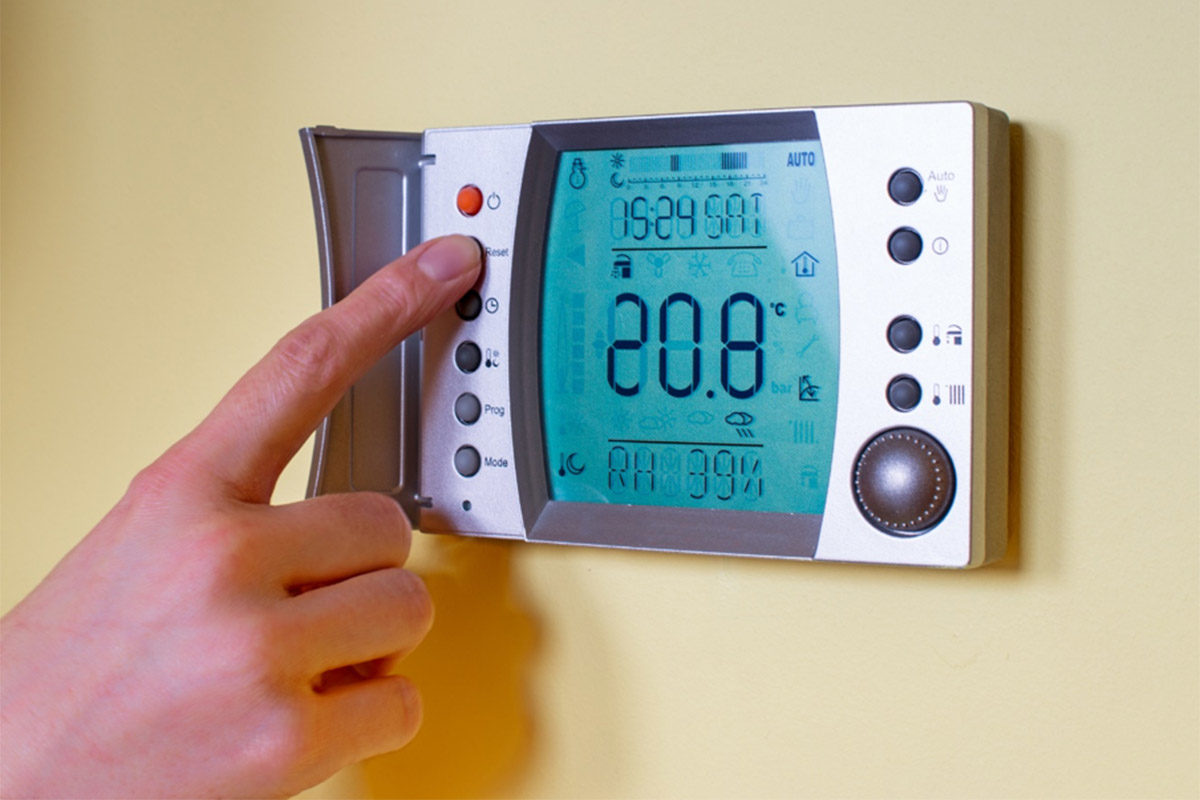 Person pressing buttons on temperature control pad