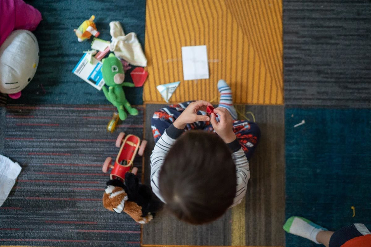 Child playing with toys on rug